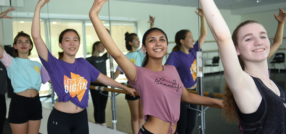 Pre-College dancers take position on the ballet bar.